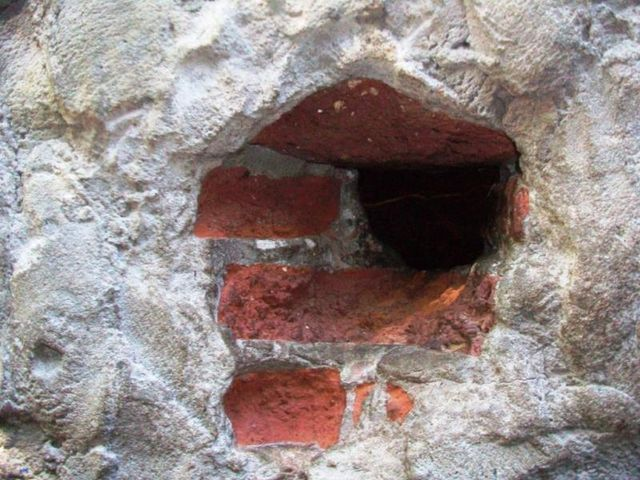 The hole in the brick wall of a *bunker,* through which a *soldadito* sell drugs