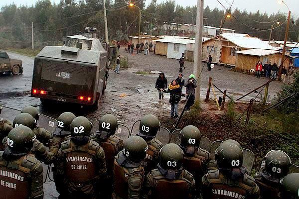 Chilean *carbineros* (rifle-bearing police) try to intimidate a Mapuche settlement