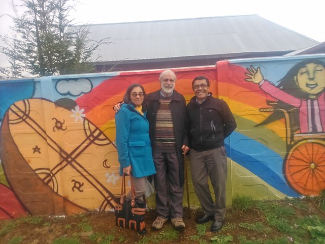 Eliana Mellado and Eduardo Herrera, director and co-directors of the School of Occupational Therapy, pose with me in front of the mural painted by members of the Union of Children and Parents for Normal Integration.