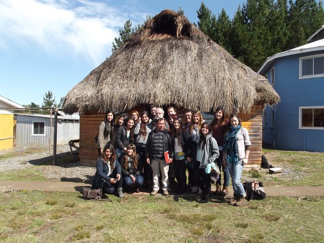 Student occupational therapist pose with the chief shaman (white pants) in front to the *ruca,* (traditional Mapuche house), which at the *Centro* is used as a meeting hall and classroom