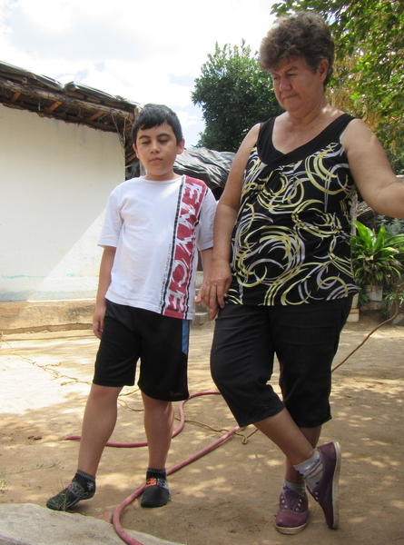 Tonio with his grandmother. His enlarged calf muscles are a key sign of Duchene's Muscular Dystrophy