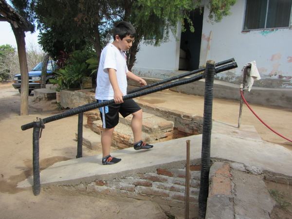This ramp, built by Tonio's grandfather, gives the boy greater independence in getting up to his home. Tree saplings wrapped with plastic irrigation tubing prevents rotting.